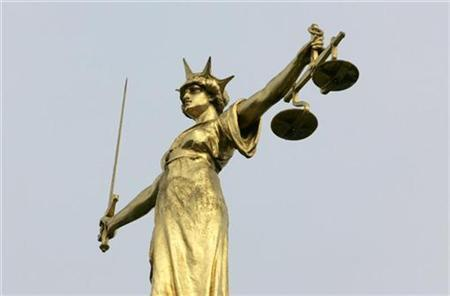 A statue representing the scales of justice is seen on the roof of the Old Bailey courts in central London, January 26, 2007. REUTERS/Toby Melville
