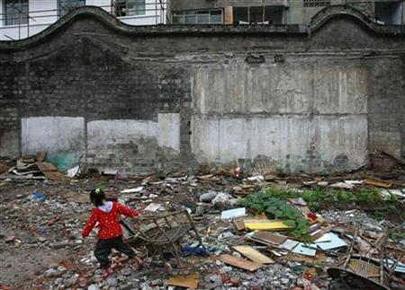 A girl plays at a demolished housing site in Suining, southwestern China's Sichuan province June 11, 2007. REUTERS/Stringer