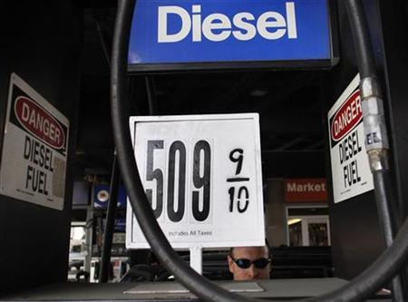 A sign advertising the cost of Diesel fuel is seen at more than $5 per gallon as a motorist prepares to pump gas into his vehicle at a gas station in New York, April 24, 2008. REUTERS/Joshua Lott