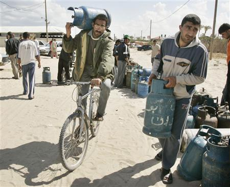 Palestinians carry cooking gas canisters to fill them outside a gas station in Rafah in the southern Gaza Strip, April 30, 2008. REUTERS/Ibraheem Abu Mustafa