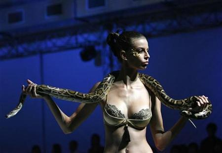 A model holds a snake on the runway as she displays a creation during Viva La Eve by Triumph at the Singapore Fashion Festival in this file photo from April 3, 2008. REUTERS/Vivek Prakash