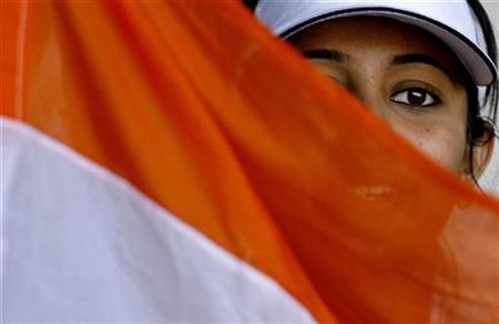 An Indian cricket fan holds the national flag as she cheers the team on the second day of the third and final cricket test match between India and Pakistan in Bangalore December 9, 2007. REUTERS/Adnan Abidi