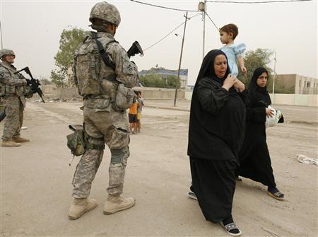 Residents walk past U.S. soldiers guarding a road in eastern Baghdad, April 30, 2008. REUTERS/Thaier al-Sudani