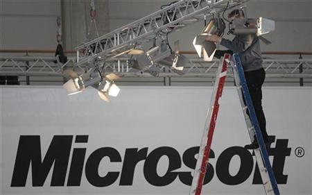 A worker fixes a spotlight at the Microsoft exhibit of the upcoming CeBIT fair in Hanover March 3, 2008. REUTERS/Hannibal Hanschke