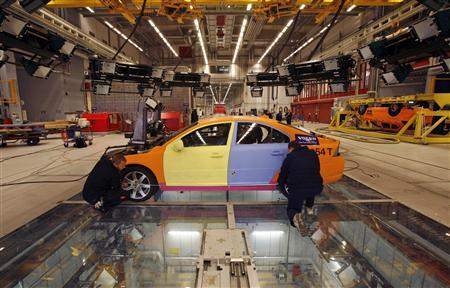 Technicians prepare vehicles for a test crash at the Volvo Safety Centre in Gothenburg April 9, 2008. The destruction of the orange sedan with its slapdash paintwork may have been intentional but it was far from wanton. It was all part of Volvo's bid to create an injury-proof car by 2020. REUTERS-Bob Strong