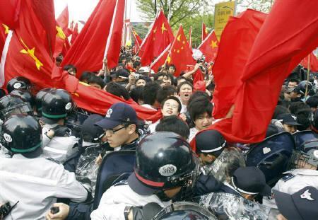 4月30日、先に当地で行われた北京五輪の聖火リレーで一部の中国人が暴力行為を行ったことを受け、韓国当局は中国人留学生などに対する査証の発行規定を厳しくする姿勢を示した。写真は27日にソウルで撮影した中国人留学生を制止する韓国警察(2008年 ロイター/Lee Jae-Won)