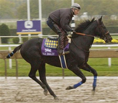 War Emblem gallops on a muddy track with exercise rider Larry Damore during the final day of early morning workouts at Arlington Park in Chicago, October 25, 2002. October 26. REUTERS/John Sommers II