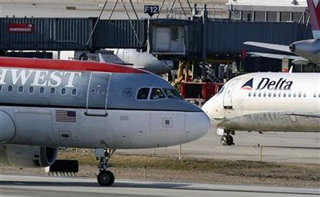 A Northwest Airlines jet and a Delta Airlines jet taxi past each other at the Minneapolis St.Paul International Airport in Minneapolis, Minnesota April 14, 2008. REUTERS/Eric Miller