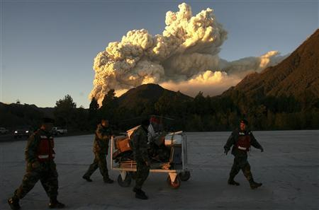 Smoke rises from Chaiten volcano as the military transport luggage at the local airdrome in Chaiten town, located some 1220 km (760 miles) south of Santiago May 4, 2008. The volcano spewed ash over Patagonian towns in southern Chile on Sunday, two days after its first eruption in thousands of years forced authorities to evacuate some 4,000 residents. REUTERS/Ivan Alvarado