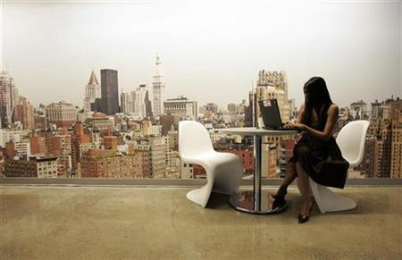 A Google employee works on a laptop in front of a mural of the New York City skyline, at the New York City company office in this March 10, 2008 file photo. REUTERS/Erin Siegal