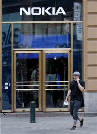 A man talking on his mobile phone walks past Nokia's flagship store in Helsinki in this August 16, 2007 file photo. REUTERS/Bob Strong