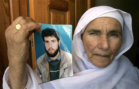 A Palestinian relative of Awad al-Qiq poses with his picture at his house in Rafah in the southern Gaza Strip, May 1, 2008. REUTERS/Ibraheem Abu Mustafa