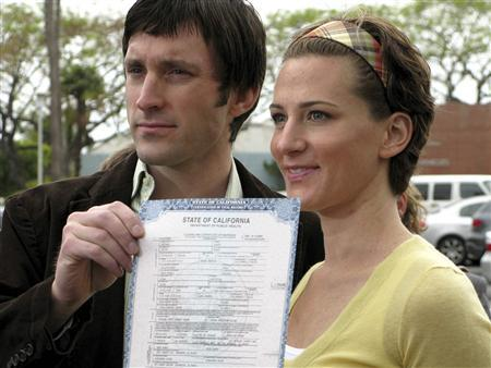 Michael Bijon (L) and his wife Diana pose with their marriage license at a news conference in Santa Monica, California May 5, 2008. REUTERS/Jill Serjeant
