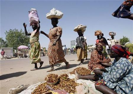 Chadian women walk past fried locust sellers at a market in Chgoua in N'Djamena November 17, 2007. REUTERS/Luc Gnago