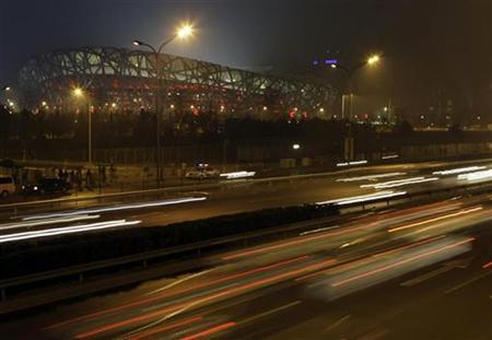 Vehicles move past the National Stadium, also known as the ''Bird's Nest,'' which is seen lit at night in Beijing April 15, 2008. REUTERS/Jason Lee