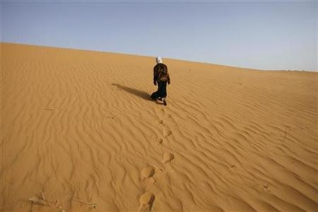A girl walks near Ouled Said ksar, a fortified village on the outskirts of the oasis town of Timimoun, about 1,200 km (745 miles) south of Algiers March 24, 2008. REUTERS/Zohra Bensemra
