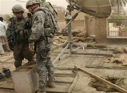 U.S. soldiers stand near a hole that damaged the roof of the BBC headquarters in Baghdad after a rocket attack, May 9, 2008. REUTERS/Sabah al-Bazee