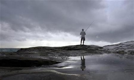 A lone fisherman fishes in the Pacific Ocean on the coast near Sydney April 9, 2008. REUTERS/Tim Wimborne