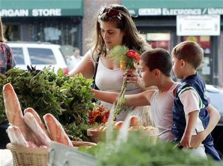 A family shops for produce in Boston in a file photo. If mothers were paid for cooking, cleaning and caring for their families they could easily earn a six-figure salary, according to new calculations. REUTERS/Brian Snyder