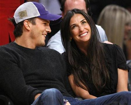 Demi Moore (R) and Ashton Kutcher watch the Los Angeles Lakers play the Detroit Pistons in an NBA basketball game in Los Angeles November 16, 2007. REUTERS/Lucy Nicholson