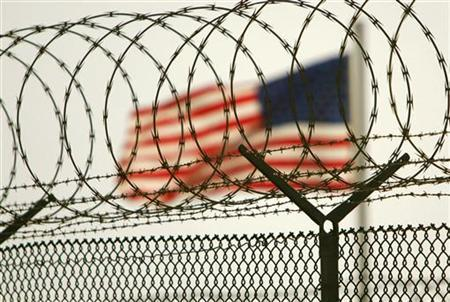 In this photo reviewed by US military officials, an American flag waves within the razor wire-lined compound of Camp Delta prison, at the Guantanamo Bay U.S. Naval Base, Cuba June 27, 2006. REUTERS/Brennan Linsley/Pool