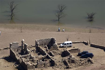 Visitors walk amid the remains of flooded village Sant Roma as it emerges from the low waters of the Sau reservoir, north of Vic near Barcelona, April 6, 2008. REUTERS/Gustau Nacarino/Files