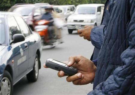 Men use their mobile phones in Jakarta January 17, 2008. REUTERS/Enny Nuraheni