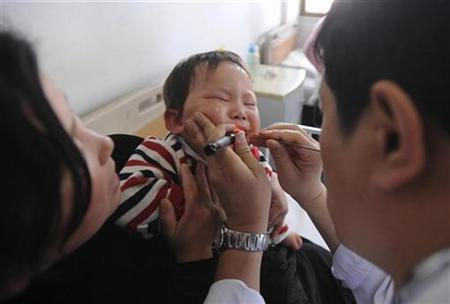 A doctor (R) examines a child for hand, foot and mouth disease infection at a hospital in Hefei, Anhui province May 11, 2008. REUTERS/Jianan Yu