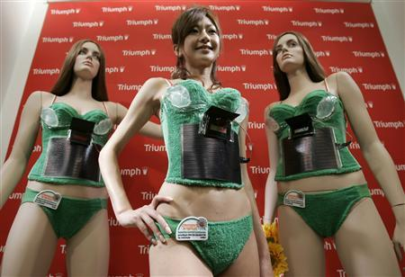 A model (C) displays lingerie maker Triumph International Japan's ''Photovoltaic-Powered Bra'' during an unveiling in Tokyo May 14, 2008. The camisole bra, which the company calls it as ''earth and human friendly'', features a solar panel which can display messages on the removable small electric board when the cell generates electricity. The bra is also equipped with pads designed to hold beverages so that the usage of cans and plastic bottles can be reduced, the company said. REUTERS/Yuriko Nakao