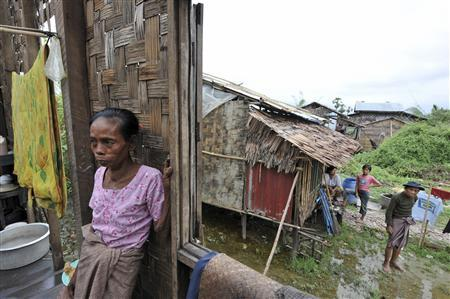 Residents stand beside their partially damaged houses in a storm devastated village near Pyapon, Myanmar, May 14, 2008. REUTERS/Ssstringer