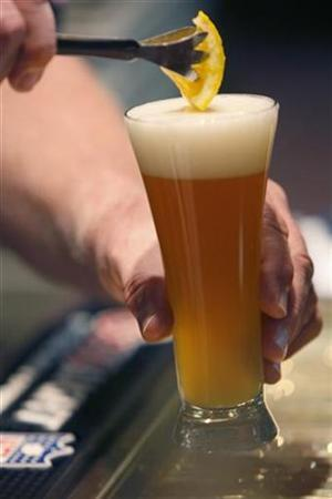 The bartender in the lounge adds a slice of orange to a beer in Golden, Colorado October 16, 2007. REUTERS/Rick Wilking