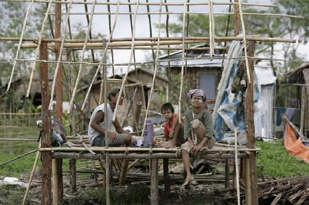 People eat lunch inside a house being rebuilt in a village affected by Cyclone Nargis located near the Myanmar capital Yangon May 14, 2008. Myanmar's army-drafted constitution was overwhelmingly approved in the first phase of a two-stage referendum after a devastating cyclone, state radio said on Thursday. REUTERS/Stringer