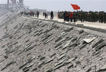 People's Liberation Army (PLA) soldiers and local residents walk across the damaged Zipingpu dam, located near the city of Dujiangyan in Sichuan province May 15, 2008. REUTERS/David Gray