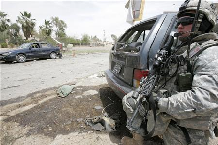 A U.S. soldier takes up position to secure the site of a bomb attack that targeted Sunni Islamic political party headquarters, which police said killed three people and wounded 23 others in Baghdad's Yarmouk district, May 14, 2008. REUTERS/Mushtaq Muhammed