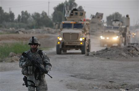 A U.S. officer walks in front of a column of vehicles from Bravo Company (Bulldogs), 1-502 Infantry Battalion during a patrol on the edge of the Shi'ite-dominated Baghdad neighbourhood of Shulla, May 12, 2008. REUTERS/Oleg Popov