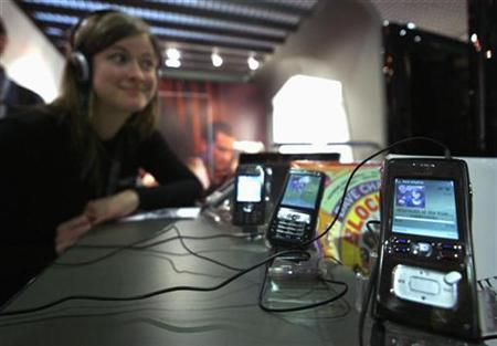 A visitor listens to music on a mobile phone at the 41st MIDEM music market in Cannes, France, January 22, 2007. REUTERS/Eric Gaillard