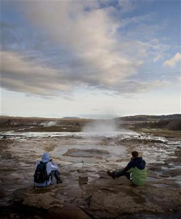 Visitors wait to take photos of a geyser eruption at a geothermal hot spring in the town of Geysir, Iceland, May 10, 2008. Iceland is the world's most peaceful nation while the United States is ranked among the bottom third, according to a study released on Tuesday. REUTERS/Bob Strong