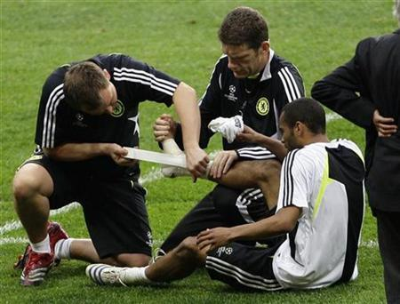 Chelsea's defender Ashley Cole receives medical help after he got injured during a practice session for the upcoming Champions League final at the Luzhniki Stadium in Moscow May 20, 2008. REUTERS/Darren Staples