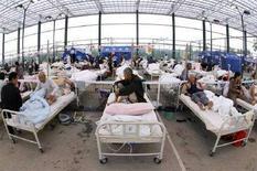 <p>Sopravvissuti al terremoto in Cina all'interno di un ospedale da campo allestito in uno stadio nella provincia di Sichuan. REUTERS/Nicky Loh</p>