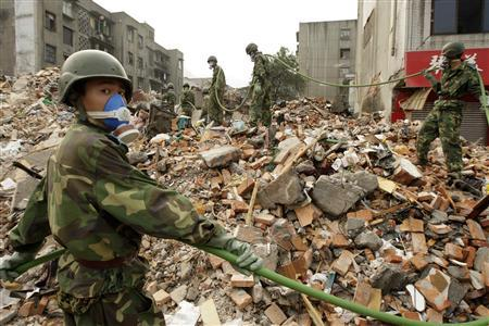 Soldiers disinfect the debris of a collapsed building in the earthquake-hit area of Hanwang, Sichuan province, May 22, 2008. REUTERS/Aly Song