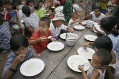 <p>Дети едят во временном центре по обеспечению населения продовольствием в Кундагоне. Мньянма, 11 мая 2008 года. Стремительный рост цен на продовольствие, который стал причиной голода, продовольственного дефицита и протестов по всему миру, представляет собой угрозу основным правам человека, сообщили в четверг представители ООН. (REUTERS/Stringer)</p>