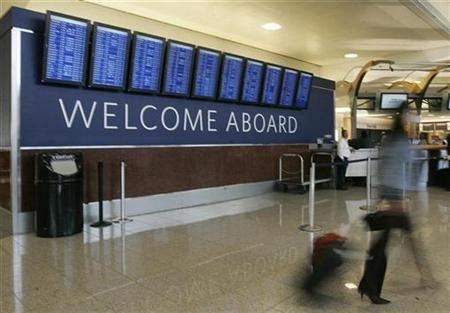 A passenger walks past a Welcome Aboard sign at the Delta Air Lines ticket counter at Hartsfield-Jackson Atlanta International Airport in Atlanta, Georgia in this April 15, 2008 file photo. REUTERS/Tami Chappell