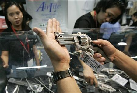 A man looks at a handgun at a sales booth on the opening day of the Defense and Sporting Arms show held in a shopping mall in Manila November 23, 2006. REUTERS/Darren Whiteside