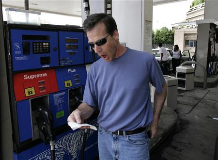 A driver playfully reacts looking at the receipt after filling his car at a gas station in Washington May 16, 2008. REUTERS/Yuri Gripas