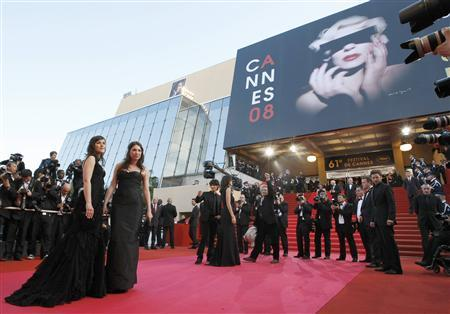 French director Philippe Garrel (C) raises his fist as he arrives on the red carpet with cast members Clementine Poidatz (L), Laura Smet (2nd L) and his son Louis Garrel (3rd L), who waves before the screening of ''La Frontiere de l'Aube'' at the 61st Cannes Film Festival May 22, 2008. REUTERS/Eric Gaillard