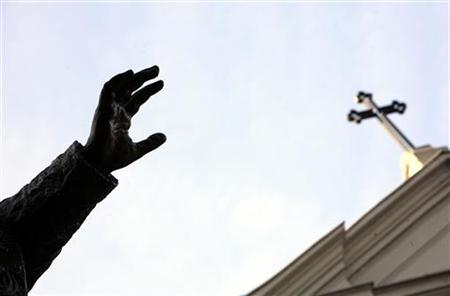 The hand of the statue of Pope Benedict XV is seen under the cross of the St. Esprit Cathedral in Istanbul November 27, 2006. REUTERS/Fatih Saribas