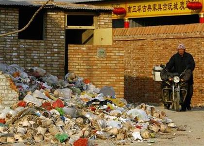 A man pushes his motorbike past a pile of plastic bags dumped in Hutong in Beijing January 9, 2008. REUTERS/David Gray