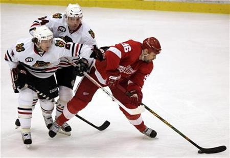 Detroit Red Wings leftwing Tomas Holmstrom (R) keeps the puck from Chicago Blackhawks center Yanic Perreault (C) and defenseman Duncan Keith during the third period of their NHL hockey game in Detroit, Michigan April 6, 2008. REUTERS/Rebecca Cook