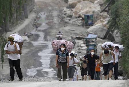 5月27日、中国四川大地震の余震とみられる揺れが続き、これまでに合わせて、42万戸の住宅が倒壊している。写真は四川省・北川で避難する地元住民ら(2008年 ロイター)