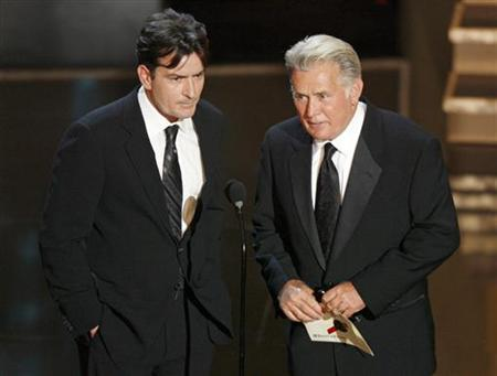Charlie Sheen (L) and his father Martin Sheen present the best supporting actress in a miniseries or movie award during the 58th annual Primetime Emmy Awards at the Shrine Auditorium in Los Angeles August 27, 2006. REUTERS/Mike Blake (UNITED STATES)